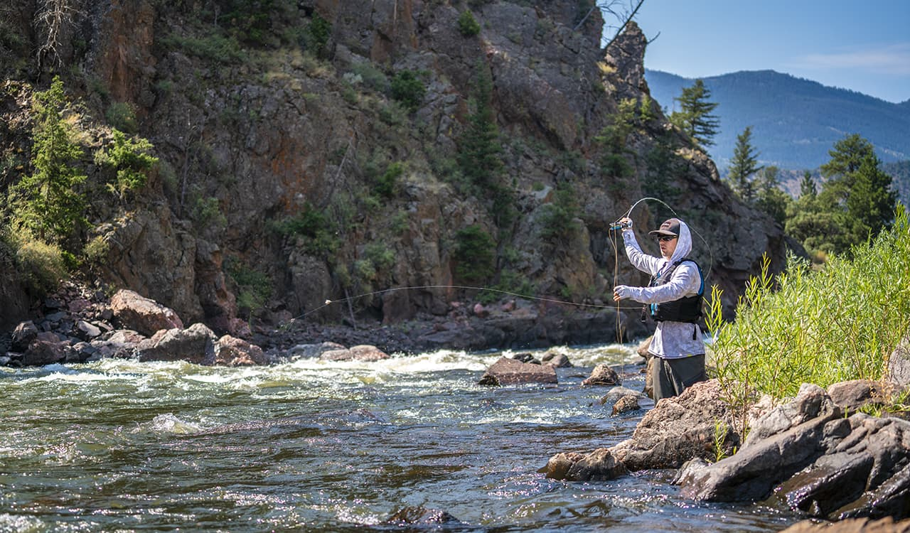 Man casting a fishing line at a river near Winter Park Resort in Colorado