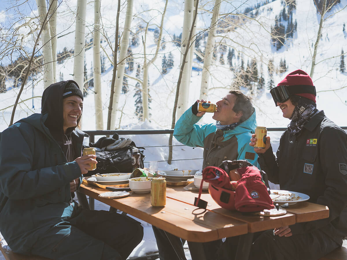 Three men sitting at a table on a patio drinking beer