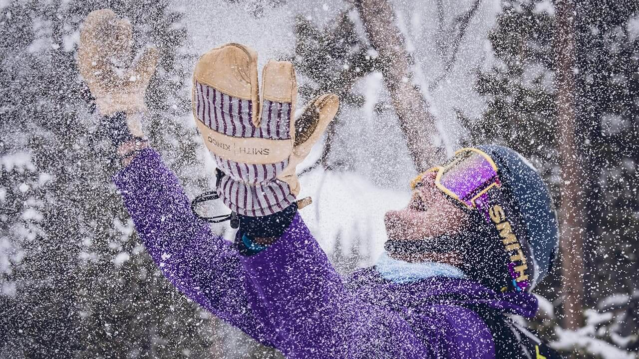 Young man in ski gear tossing snow in the air