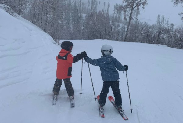 Two young boys in ski gear giving each other a high five on a snowy day on the mountain