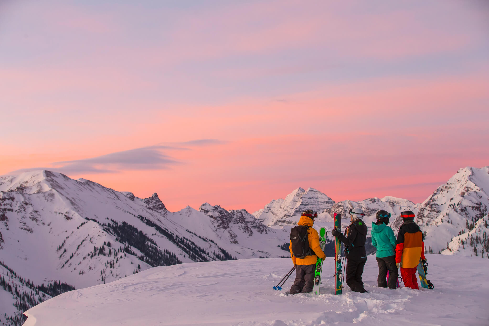 A group of four skiers and snowboarders looking out at the Maroon Bells at sunset