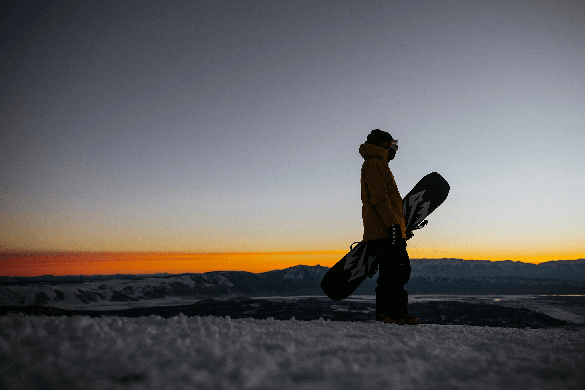 Man holding a snowboard watching the sunrise on top of a mountain ski slope